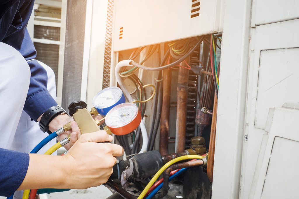 AC Repair Services - Technician is checking air conditioner